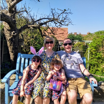 Photograph of Tara Luke sitting on a bench with her 2 daughters and husband