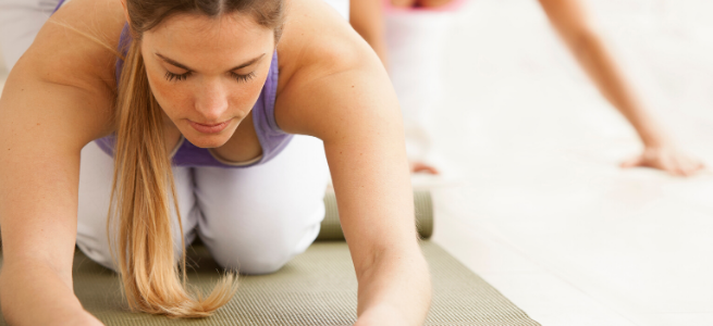 women kneeling and learning forward in a yoga pose